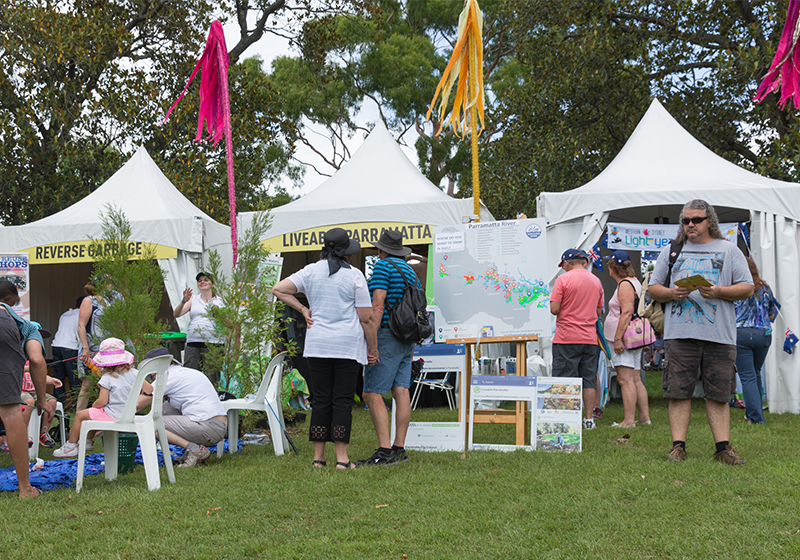 Row of three white event booths at Australia Day with residents gathering at the front