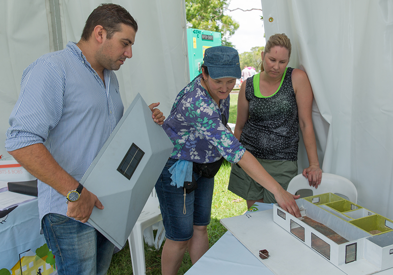 Steven Issa holds model house roof while Nicole Miller points at model house and Michelle Playford looks on - all are inside the event booth