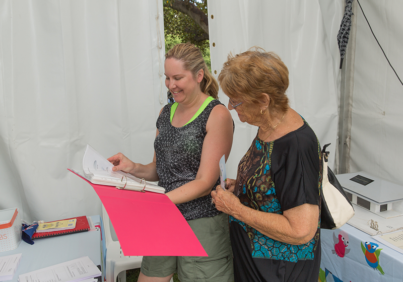 Michelle Playford with a resident - they looks at a pink folder while standing inside the event booth