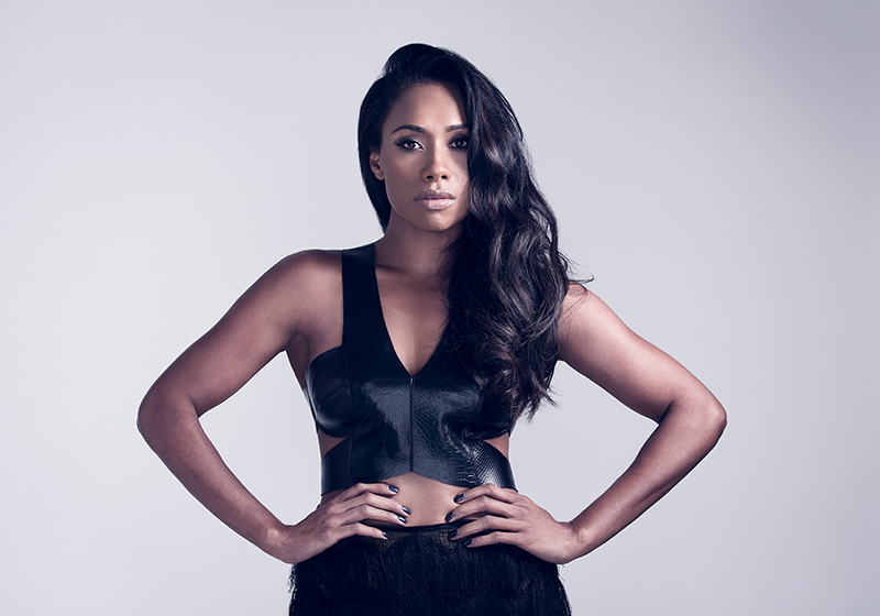 Paulini stands with hands on hips while wearing black dress
