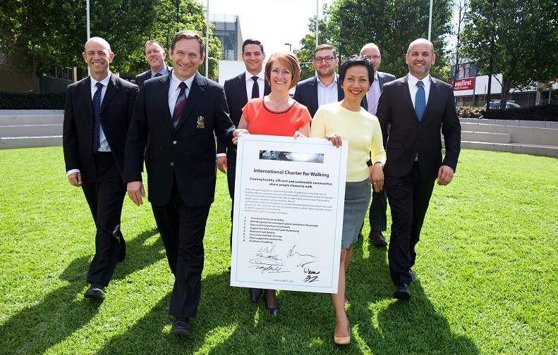 Western Sydney mayors walking in a group with an oversized copy of the International Charter for Walking.
