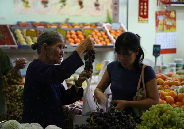 Women buying fruit at grocery store.